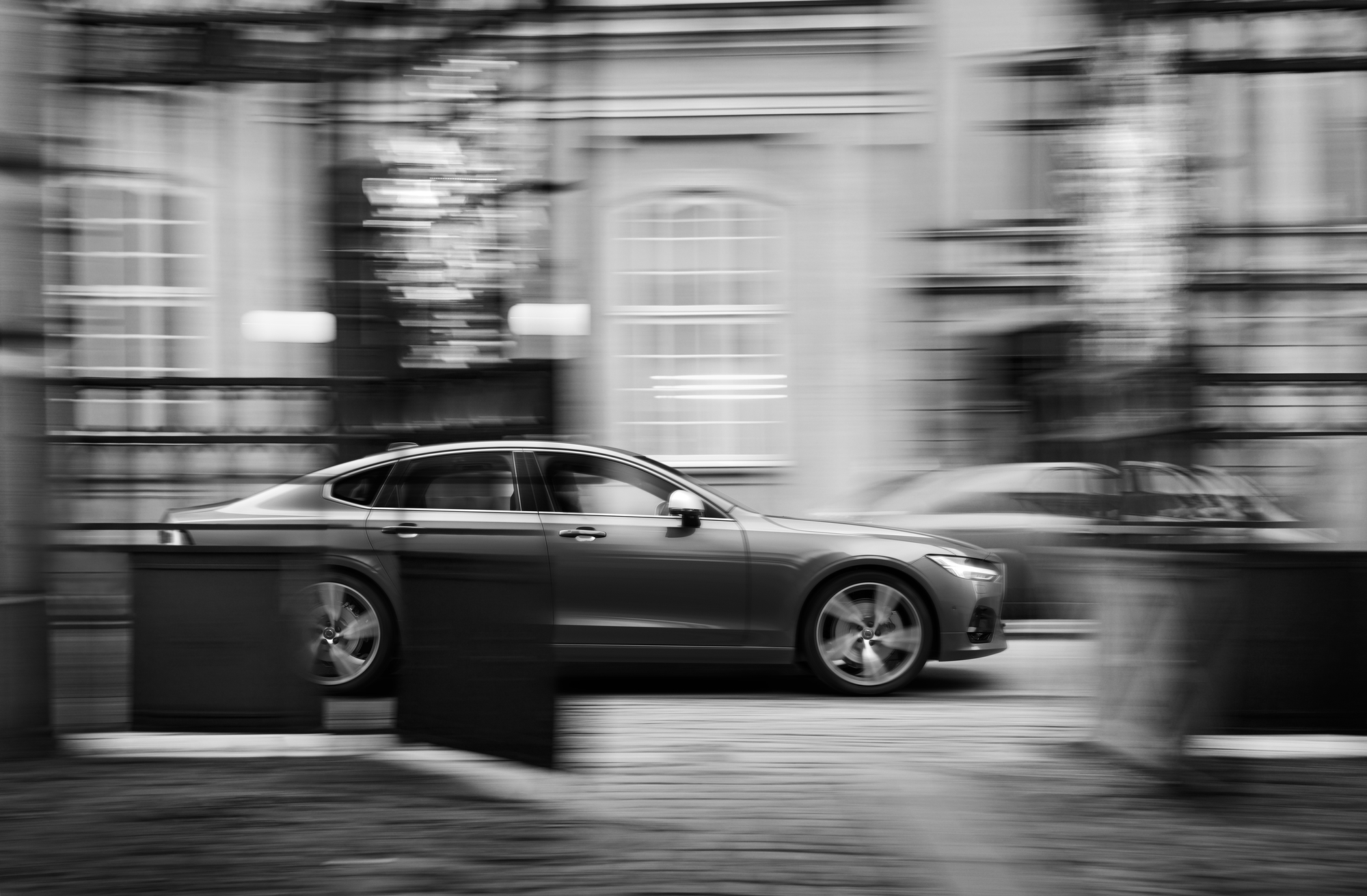 Volvo V90 R in blue black and white picture driving by some buildings- Blurry pictur