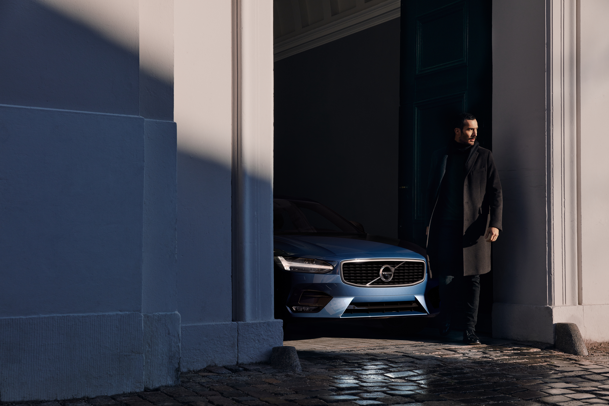 Front of Volvo V90 R in blue. Rest i hiding inside a building. Man leaning against wall next to it