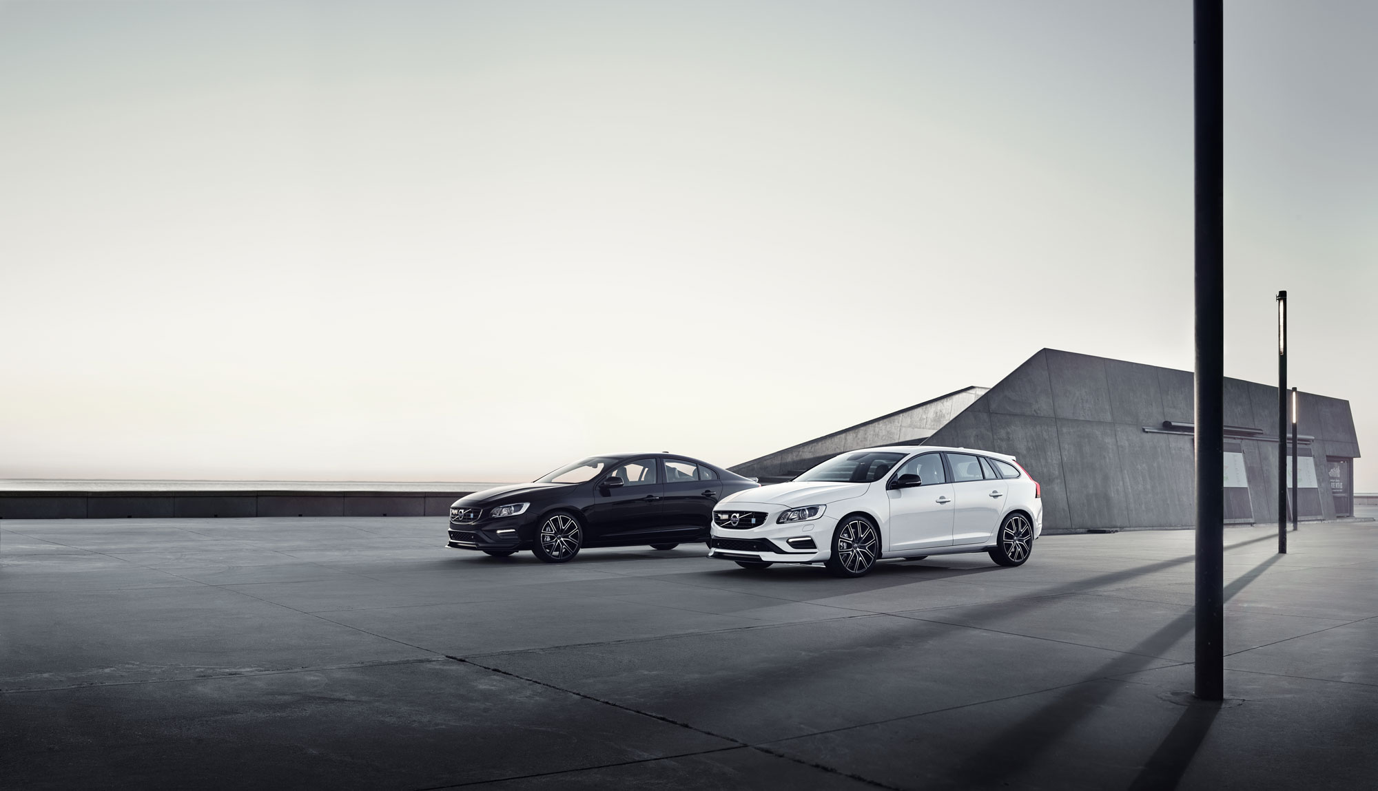 Dark and white Volvos parked on concrete. In background a bit of concrete building and sky