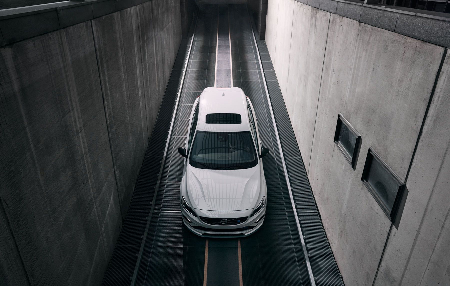 White Volvo driving on a road down something. Cement walls on each side