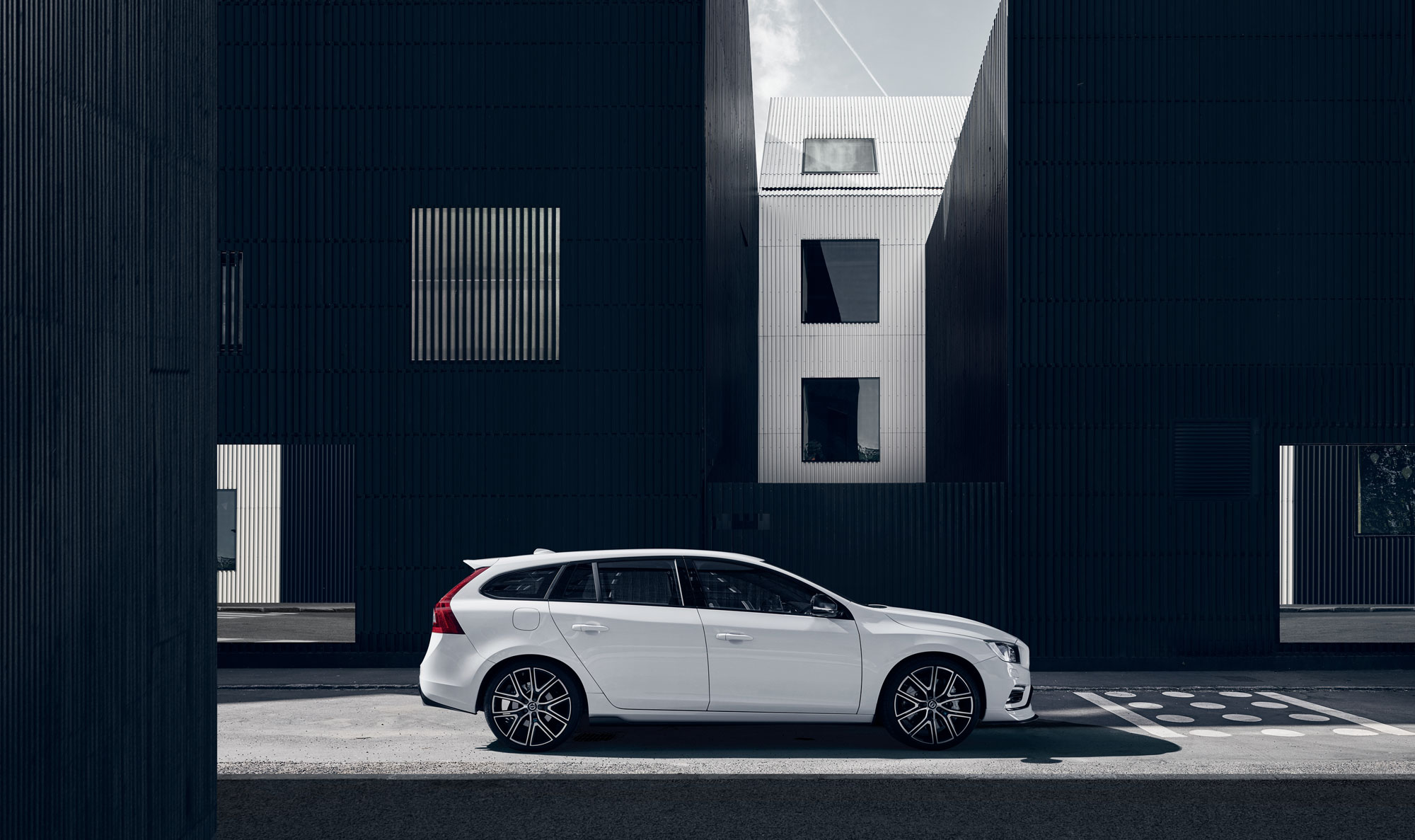White Volvo in front of a black and white building