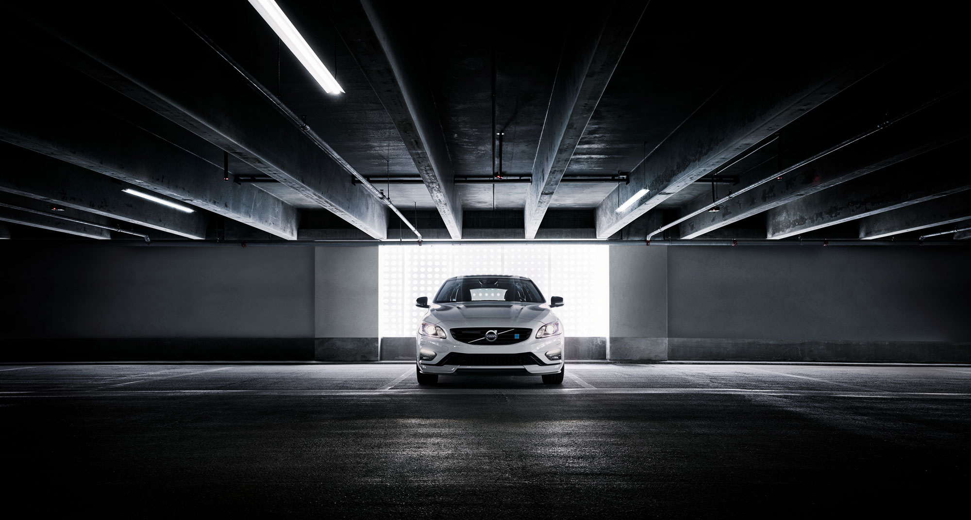 White Volvo parked in a parking garage. Parking in front of a widow opening