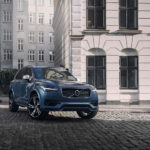 Volvo XC90 sup in blue parked on cobblestone with classic looking buildings in background